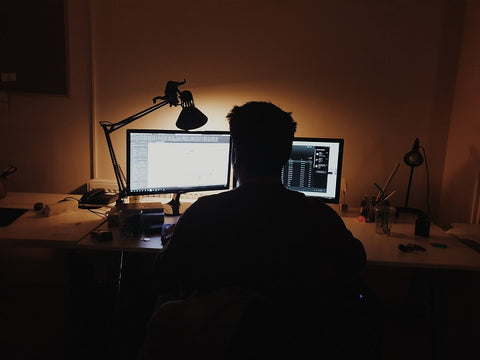 man working on his computer at night