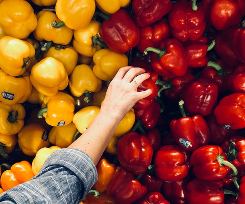 hand picking fresh red bell peppers