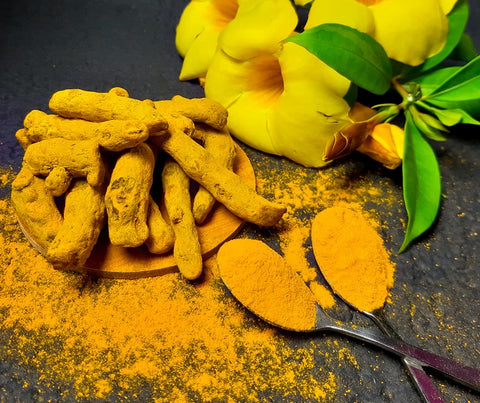 turmeric powder in spoons with roots and flowers closeup
