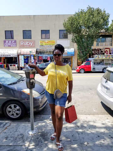 Black woman taking a picture on the streets wearing Yellow California T-Shirt and denim Bermuda shorts, sun glasses, YSL Camera bag, and holding a shopping bag.