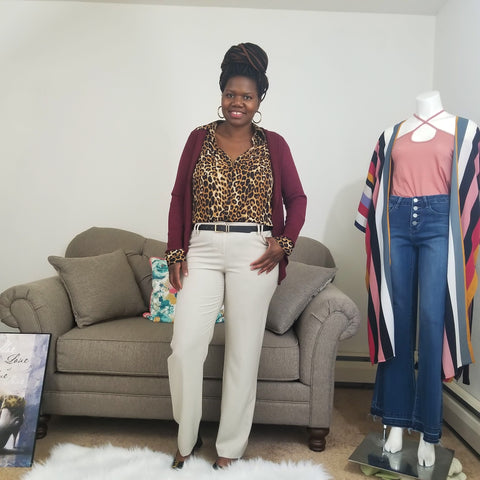 black woman with a box braid bun leopard shirt burgundy cardigan and tan pants