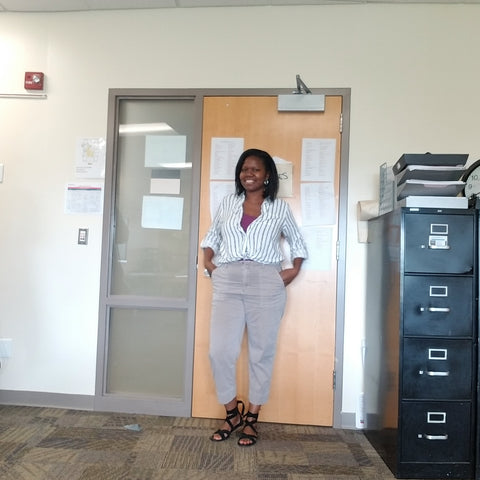 Teacher standing in classroom. Black woman, tan pants, striped shit, black sandals.