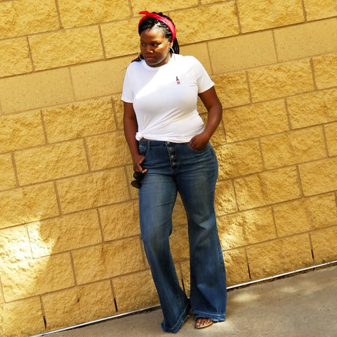 black woman white t-shit wide leg blue jeans red bandanna on head sun glasses leaning on wall