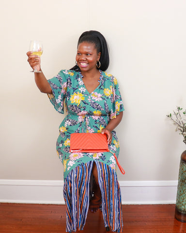 Black woman in floral dress having a toast