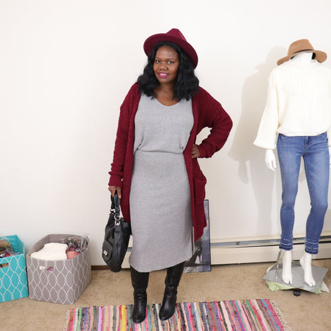 black woman, burgundy hat and cardigan, grey skirt set, black boots and purse.