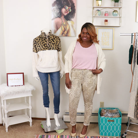 black woman wearing Leopard Print Pants, Cream cardigan, nude pumps, pink shirt