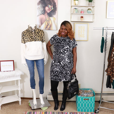 black woman, leopard print shift dress, black tights, black knee high boots, black bag