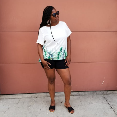 Black woman taking photos in white floral shirt, black shorts, sun glasses, and black sandals.