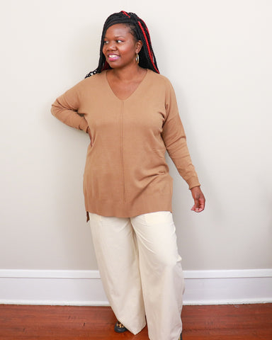 Black woman wearing long sleeve camel colored sweater, taupe colored wide leg pants, and leopard print shoes.