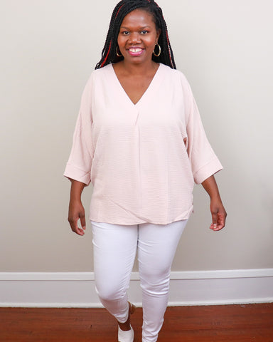 Black woman smiling wearing white skinny jeans, light pink woven top, and white mules.