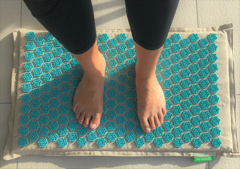 Someone stands on the blue acupressure mat