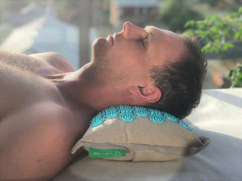 A man lies on the acupressure pillow blue