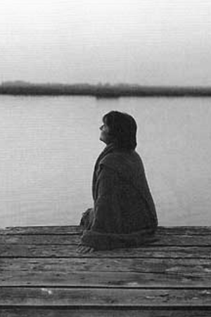 Rina Menardi sitting on dock at lake