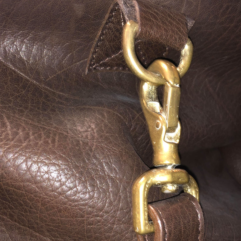 Close up view of one of the high-quality metal clasps that connects the strap to the bag.