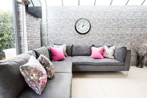 large kitchen sofa with brick wallpaper bright pink cushions