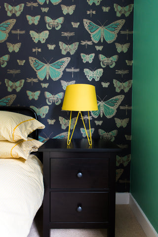 bedroom with butterfly wallpaper yellow lamp arsenic walls