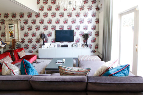 Living room design with feature wall of cole and son wallpaper, romo velvets, the sofa and chair furniture in reds and teals