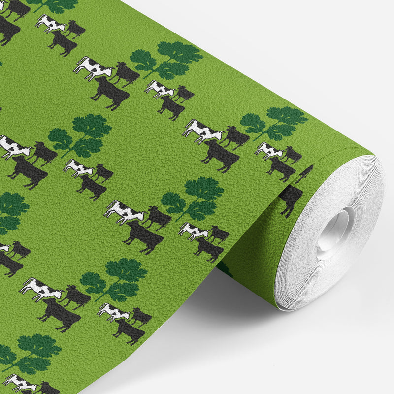 roll of Green wallpaper with black and white cows standing around some green parsley