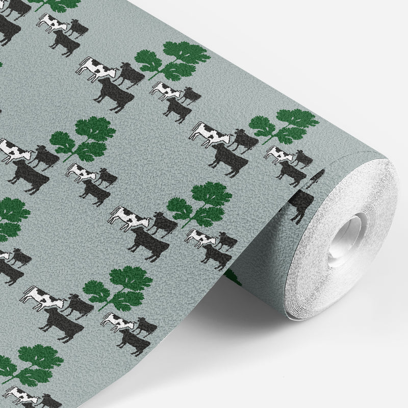 roll of Grey wallpaper with black and white cows standing around some green parsley
