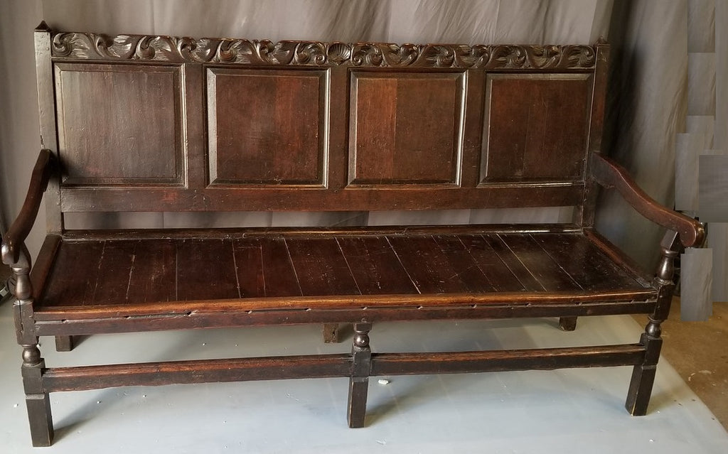 EARLY DARK OAK ENGLISH BENCH WITH ARMS AND A CARVED CREST RAIL