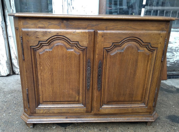 SMALL CANTED CORNER OAK SERVER WITH ARCHED DOORS