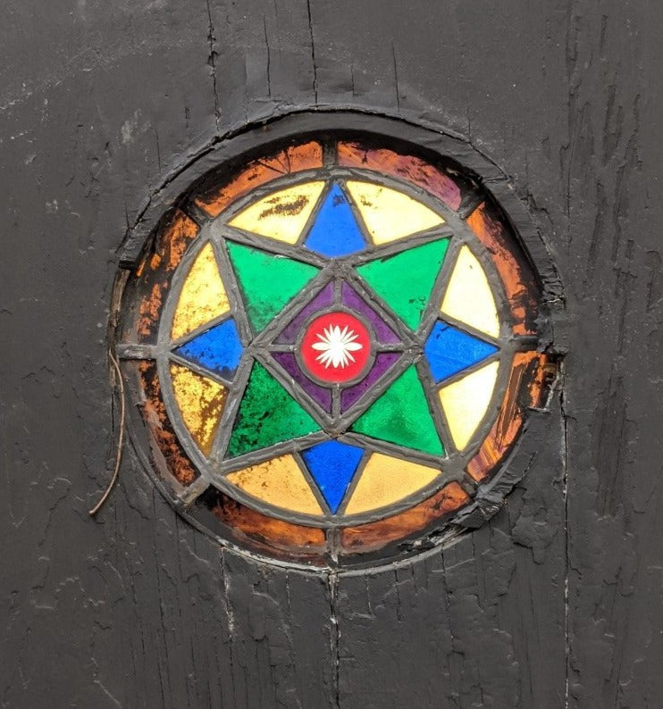 BLACK AS IS DOOR WITH COOL ROUND STAINED GLASS INSETT
