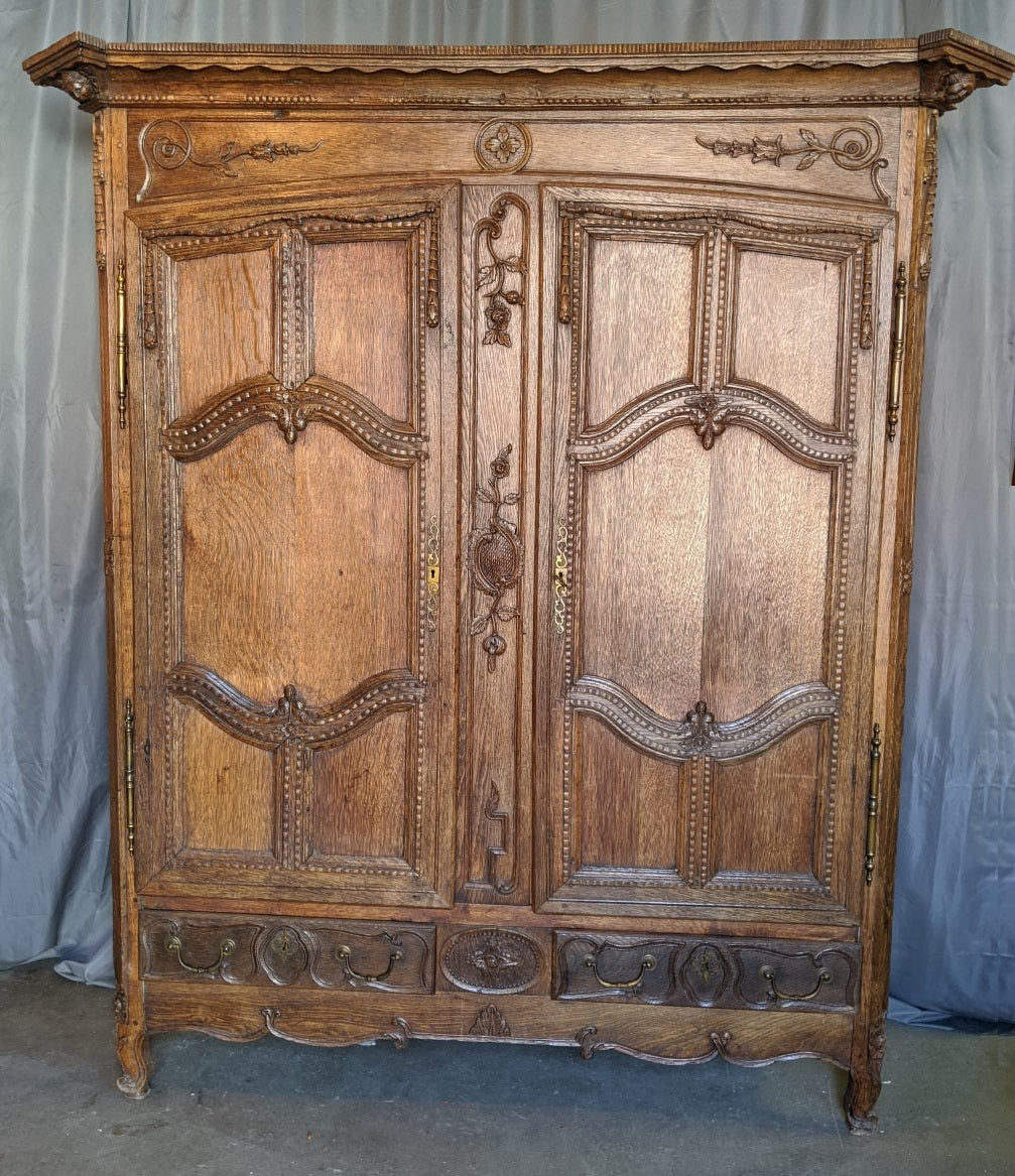 ORNATELY CARVED LOUIS XV OAK ARMOIRE WITH CHERUB HEADS