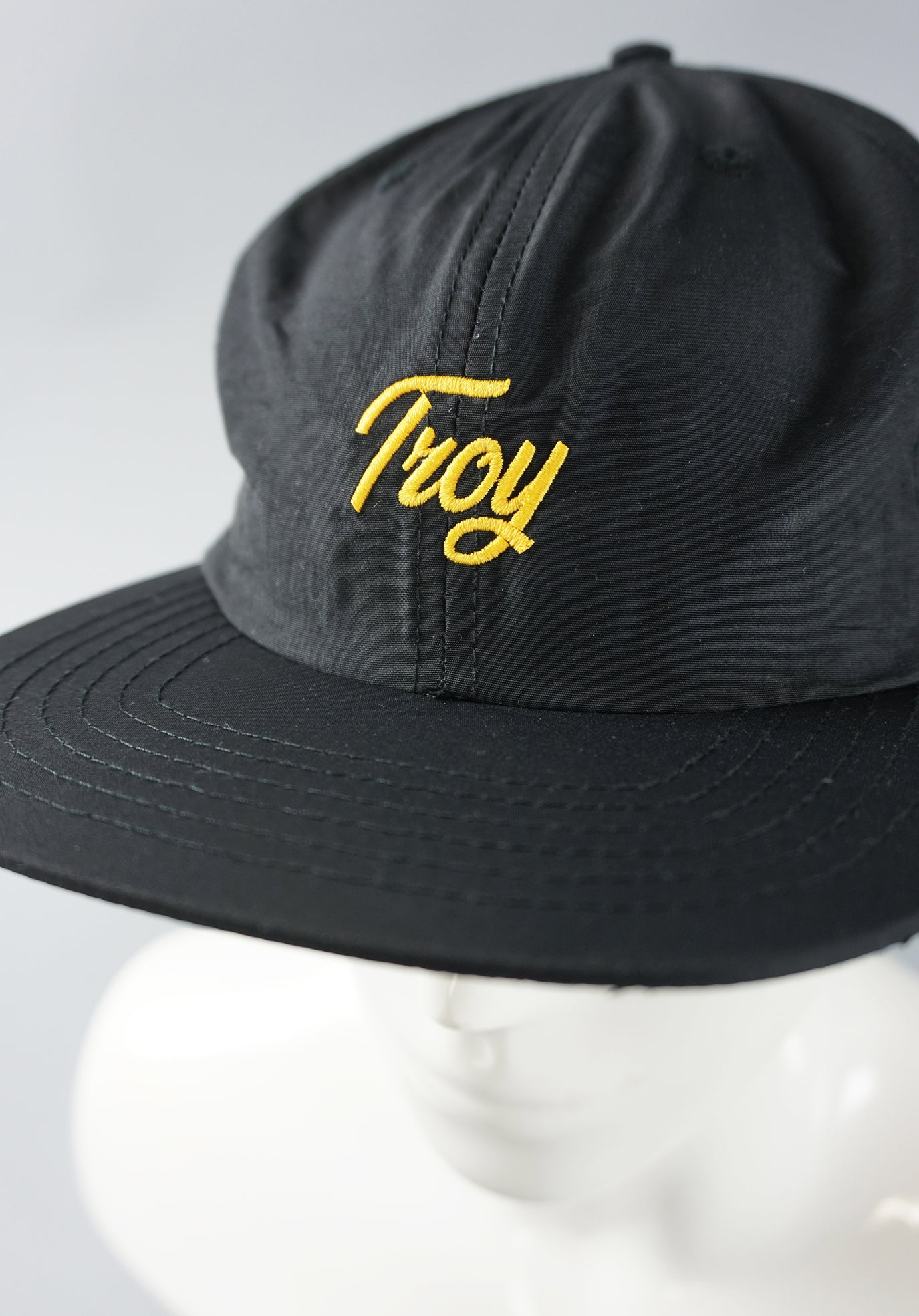 Close up of Troy script cap and gold embroidery.