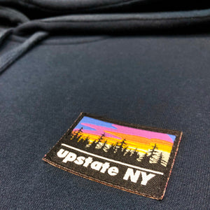 A big statement on a small patch! Our custom-woven Upstate NY patch features a stylized sunrise over a forest skyline. The patch is sewn to the front left chest of a navy blue pullover hooded sweatshirt.  Only found at 518 Prints