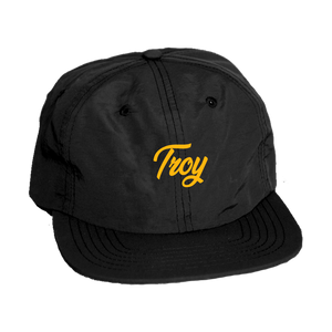 Keep your noggin dry in our custom-embroidered Troy simple script cap. Design is embroidered in gold on the front of a black nylon adjustable cap.  Only found at 518 Prints