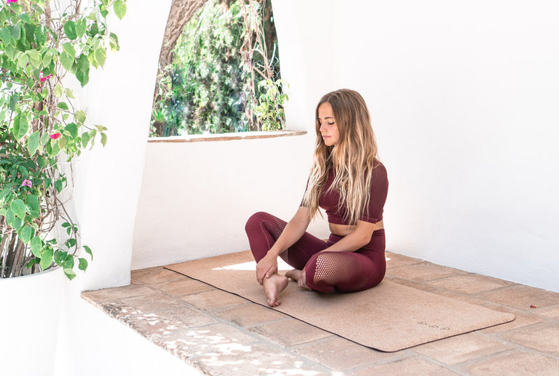 girl sitting on cork yoga mat