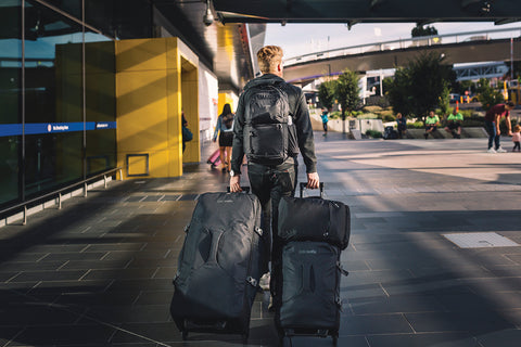 Man at airport wheeling two Pacsafe luggages