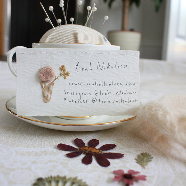 embroidered business card, pressed flowers in room