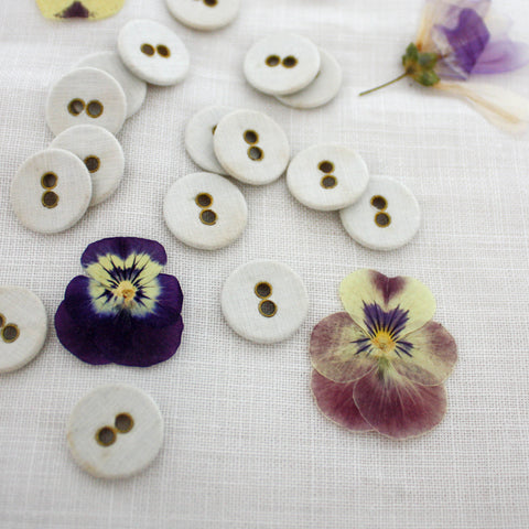 Linen buttons and pressed flowers on a linen cloth