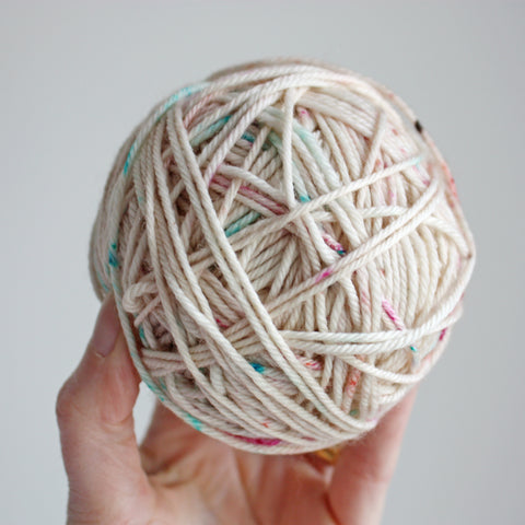 Ball of hand dyed wool held in hand