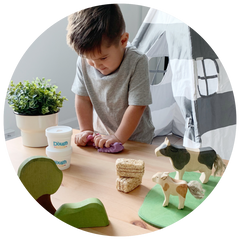 young boy playing with purple dough on table with wooden farm animal toys and trees