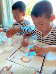 Two boys playing with dough to make organs for school