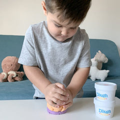 little boy playing with dough with stuffed animals in the backgorund