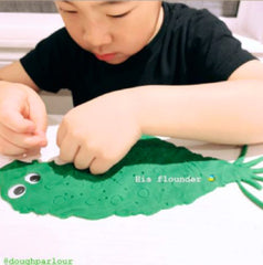 little boy making flounder out of dough