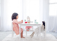 little girl sitting at table playing