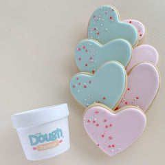 Heart shaped sugar cookies decorated in green and pink beside tub of play dough
