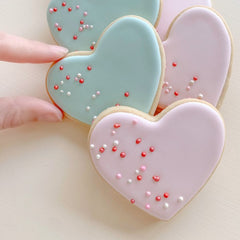 Heart shaped sugar cookies decorated in green and pink
