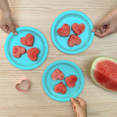 watermelon cut into heart shapes on blue plates