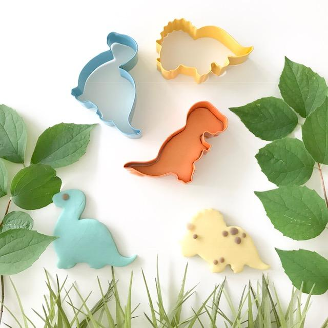 An adorable set of dino cutters that includes an orange t-rex, a yellow triceratops and a blue brachiosaurus showing how the dough is cut out using them on a table with leaves and grass