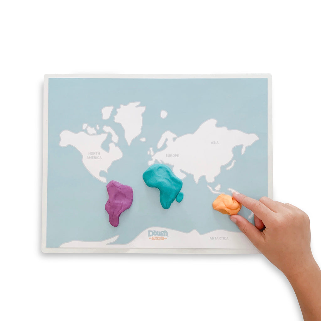 Child playing with the World Continents mat with dough