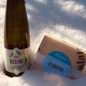 Bottle of wine and slice of cheese displayed in the snow
