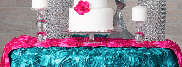 easy event fabrics in turquoise and fuchsia satin rosette tablecloths and table runners on a cake table