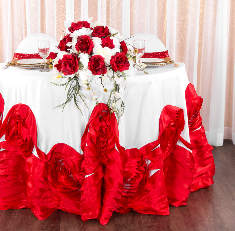 Sweetheart Table Decor with red and white rosette tablecloth with gold napkins, drapes, and charger plates