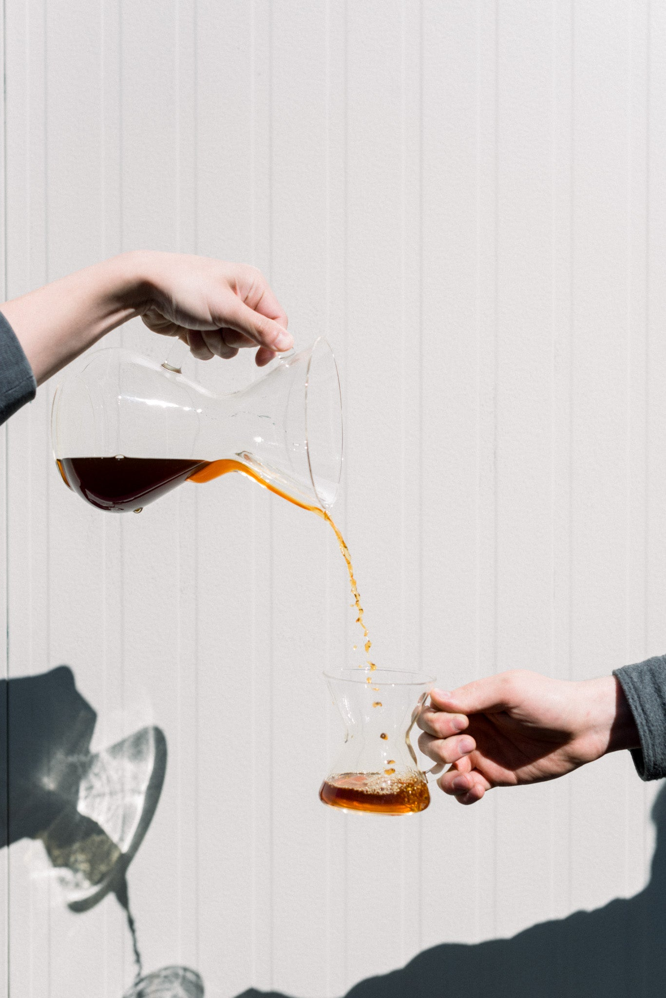 Coffee pouring from pitcher into smaller mug