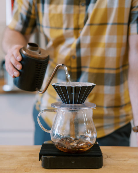 Man pouring water into Origami dripper making ice brew coffee